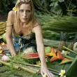 Stock Photo: Young woman sitting on a bed of tropical fruits in an exotic garden.