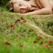 Stock Photo: Beautiful blonde womlaying naked on green grass and tree roots