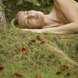 Nude young woman laying down on green grass and red rose petals — Stockfoto