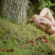 Beautiful blonde woman laying naked on green grass and tree roots — Stock Photo #21105047