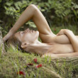 Nude young woman laying down on green grass - Stock Photo