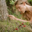 Stock Photo: Beautiful blonde woman laying naked on green grass and tree roots.