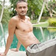Oung man sitting by the edge of a swimming pool in a travel destination hotel spa — Stock Photo #21105083