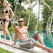 Sexy young couple relaxing by an exotic swimming pool in a tropical destination hotel — Stock Photo