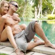 Sexy young couple lounging on the edge of an exotic swimming pool — Stock Photo