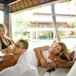 Two attractive young couples lounging on an outdoors exotic bed — Stockfoto