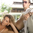 Young couple lounging on an outdoors tropical bed in an exotic hotel spa garden — Stock Photo #21105183