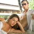 Stock Photo: Exy young couple lounging on outdoors tropical bed