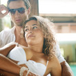 Sexy young couple lounging on an exterior tropical bed — Stock Photo