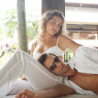 Foto Stock: Young couple lounging on exotic lounger bed
