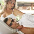 Sexy young couple hugging while lounging together on a tropical garden bed — Stok fotoğraf