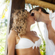 Attractive sexy couple kissing while lounging on garden bed — Stock Photo #21105289