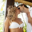 Attractive sexy couple kissing while lounging on a garden bed — Stock Photo