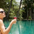 Young woman drinking a cocktail while sitting by the edge of a tropical swimming pool — Stock Photo #21105477