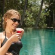 Young woman drinking a cocktail while sitting by the edge of a tropical swimming pool — Stock Photo #21105493
