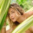 Beautiful young woman looking through large tropical leaves while on vacation in an exotic hotel destination near a swimming pool. — Stock Photo #21105643