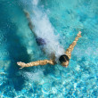 Man diving into a swimming pool, forming an arrow shape and leaving a trace behind him. - Stock Photo