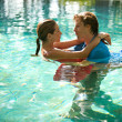 Sexy young couple submerged in a swimming pool while dressed, hugging and kissing while on a tropical destination vacation. — Stock Photo #21105875
