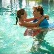Sexy young couple submerged in a swimming pool while dressed, hugging and kissing while on a tropical destination vacation. — Stok fotoğraf
