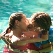 Exy young couple submerged in a swimming pool while dressed — Stock Photo #21105907