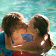 Stock Photo: Sexy young couple submerged in a swimming pool while dressed