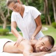 Young masseuse massaging an attractive man in a tropical hotel garden near a swimming pool. — Stock Photo