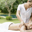 Young man receiving a massage in a tropical garden near a swimming pool. — Stock Photo #21105987