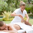 Photo: Young masseuse massaging and stretching body of attractive min tropical hotel garden