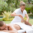 Young masseuse massaging and stretching body of attractive min tropical hotel garden — Stok Fotoğraf #21105993