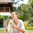 Attractive young woman smelling tropical flowers in an exotic spa garden. — Stock Photo #21106013