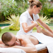 Young masseuse massaging and stretching the body of an attractive man in a tropical hotel garden near a swimming pool. — Stock Photo #21106019