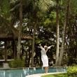 Young woman standing at the edge of a swimming pool surrounded by tall palm trees - Stok fotoğraf