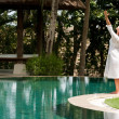 Young woman's figure with arms outstretched while standing at the edge of a swimming pool in a tropical nature location. — Stock Photo