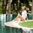 Attractive young woman sitting down at the edge of a swimming pool - Stock Photo