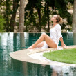 Attractive young woman sitting down at the edge of a swimming pool — Stock Photo