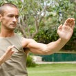 Attractive young man focused on doing his martial arts training in a tropical garden. — Stock Photo