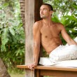 Young attractive man relaxing on a sun lounger while on vacation in a tropical destination. — Stock Photo #21106227