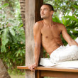 Young attractive man relaxing on a sun lounger while on vacation in a tropical destination. — Stock Photo
