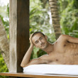 Portrait of a young man relaxing on an outdoor spa bed in a tropical garden smiling. — Stock Photo #21106259