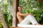 Attractive man relaxing on a sun lounger — Stock Photo