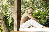 Topless young man sitting on a wooden garden bed during a tropical vacation. — Stock Photo