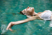 Attractive young woman floating on a spa's swimming pool — Stock Photo