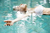 Attractive young woman floating in a swimming pool with her arms outstretched. — Foto de Stock