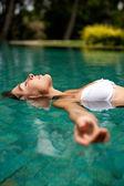 侧视图漂浮在一个游泳池、 有魅力的年轻女人的微笑. — 图库照片