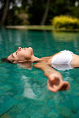 Side view of an attractive young woman floating on a swimming pool, smiling. — Stock Photo
