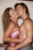 Attraktives paar liebhaber im bett wird intim miteinander und küssen. — Stockfoto