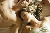 Attractive young couple laying down in bed — Stock Photo
