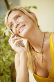 Young woman having a conversation on a cell phone in a home garden. — Stock Photo