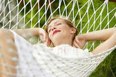 Young attractive woman laying and relaxing on a white hammock in a garden. — Stock Photo