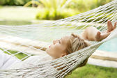 Young woman laying down and relaxing on a white hammock — Stock Photo